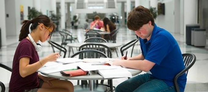 two students studying at a table in the UBCFA atrium.